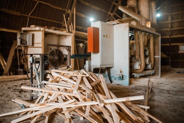 Stapel planken in de buurt van houtbewerkingsmachine in zaagsel, niemand, houtindustrie, timmerwerk. houtverwerking op fabriek, boszagen in houtzagerij, zagerij