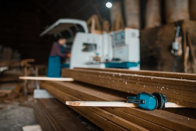 Stapel planken, timmerman in uniform op houtbewerkingsmachine, houtindustrie, timmerwerk. houtverwerking op fabriek, boszagen in houtzagerij, zagerij
