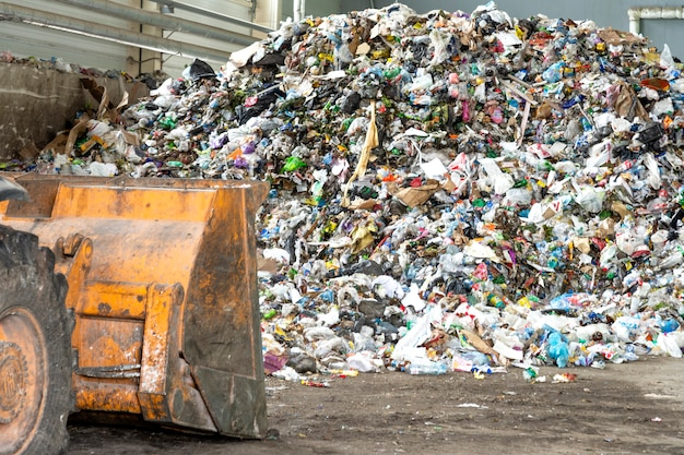 Stapel plastic flessen, papier en polyethyleen in een afvalrecyclingfabriek voordat u ze sorteert