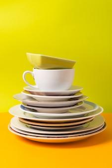 Stapel platen, servies op kleurrijke achtergrond.