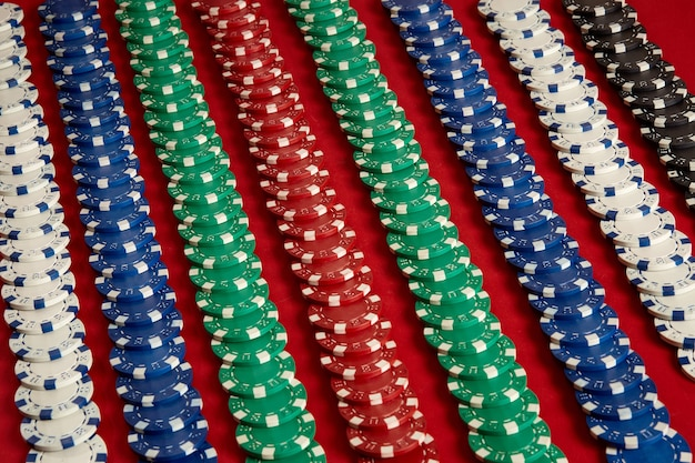 Stapel pokerfiches op rode achtergrond bij casino. bovenaanzicht. ruimte kopiëren. stilleven. plat leggen