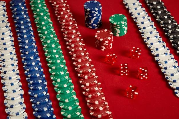 Stapel pokerfiches op rode achtergrond bij casino