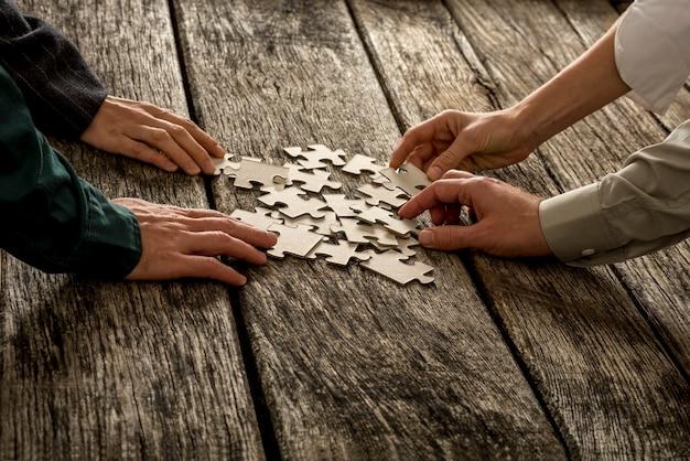 Stapel puzzelstukjes liggend op een gestructureerd houten bureau met vier handen, mannelijk en vrouwelijk, reikend naar elk een nemen. conceptueel teamwerk en strategieplanning.