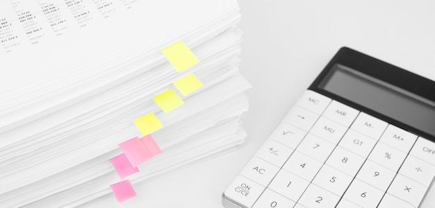 Stapel rapport financiële gegevens met vergrootglas en rekenmachine. concept van zaken, financiën en data-onderzoek.