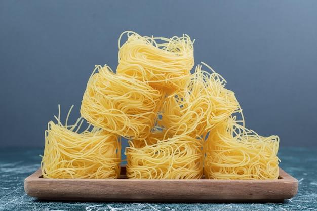 Stapel rauwe spaghetti nesten op een houten bord.