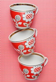 Stapel retro kopjes met rode patronen op tafelkleed met stippen