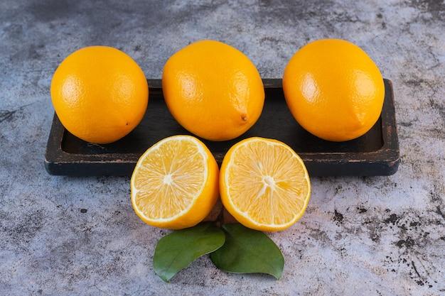Stapel rijpe citroenen op een houten bord over grijs.