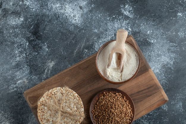 Stapel rijstwafels, kom bloem en boekweit op een houten bord