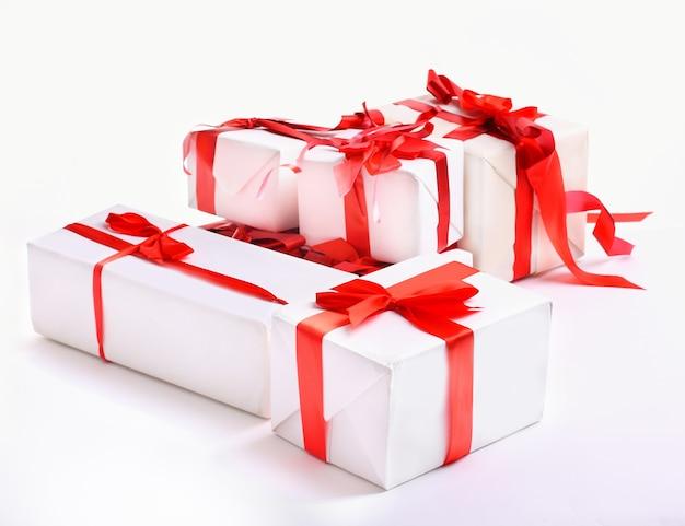 Stapel rode geschenkdozen versierd met strik op wit wordt geïsoleerd