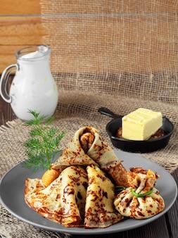Stapel russische pannenkoeken met boter en verse zure room