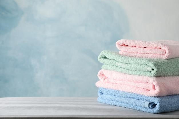 Stapel schone handdoeken op strijkplank,