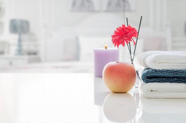 Stapel schone handdoeken op witte lijst met onduidelijk beeld van bedruimte.