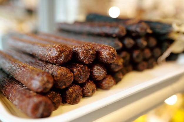 Stapel smakelijke en pittige verse worstjes tentoongesteld met vleesproducten in grote hedendaagse supermarkt