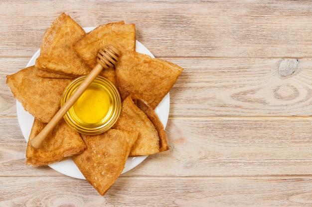 Stapel smakelijke pannekoeken met honing in kruik op houten lijst met copyspace