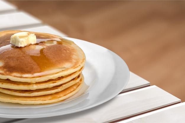 Stapel smakelijke pannenkoeken met boter op plaat