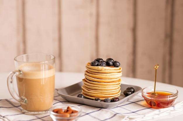 Stapel smakelijke zelfgemaakte pannenkoeken met bramen bovenop, omringd door een glas latte en twee kommen met honing en amandel