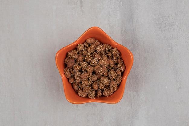 Stapel snoepjes met sesamzaadjes in oranje kom.