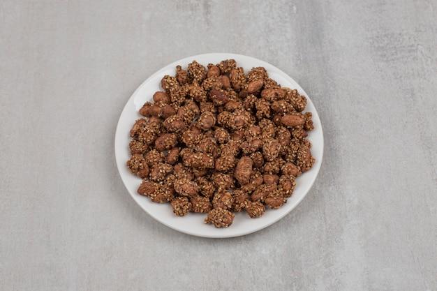 Stapel snoepjes met sesamzaadjes op witte plaat.