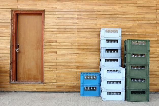 Stapel soda plastic blauwe, groene kleur krat aan de achterkant van bar pub met grote mooie houten muur en deuren op betonnen vloer