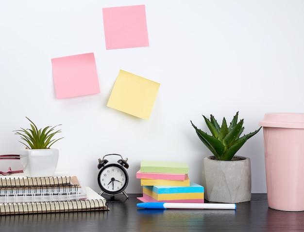 Stapel spiraalvormige notitieboekjes en gekleurde stickers, naast een keramische pot met een bloem op een zwarte tafel