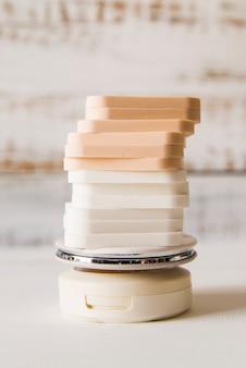 Stapel sponsen op compact poeder op witte achtergrond