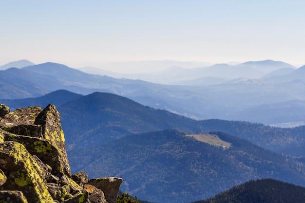 Stapel stenen die met mos bovenop een berg op bergenachtergrond worden behandeld. concept van evenwicht en harmonie. stapel zenrotsen. wilde natuur en geologiedetail.