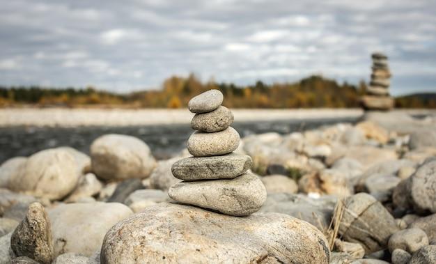 Stapel stenen gebouwd in steenhoop op de achtergrond van de rivier. rust en onthechting met de natuur