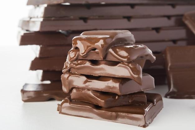 Stapel stukken van smeltende chocolade met grote stapel van chocolade op achtergrond