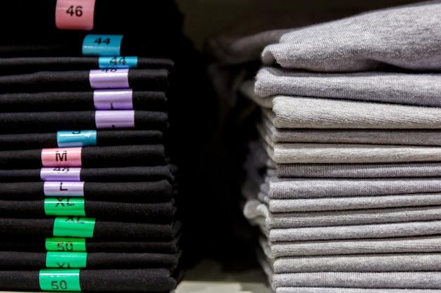 Stapel t-shirtkleding op plank in winkelcentrum of boetiek met maten