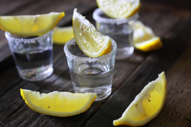 Stapel tequila met zout en citroen op een houten achtergrond