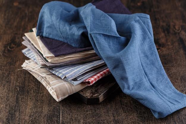 Stapel textiellinnen servetten van verschillende kleuren.