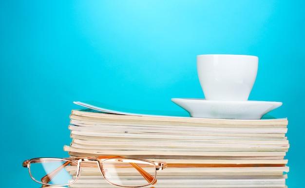 Stapel tijdschriften, kop en glazen