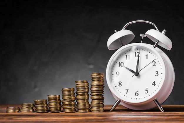 Stapel toenemende munten met witte wekker op houten bureau tegen zwarte achtergrond