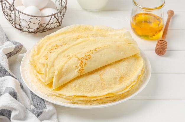 Stapel traditionele dunne pannenkoeken of pannenkoeken op een plaat met honing en zure room op een witte houten achtergrond.