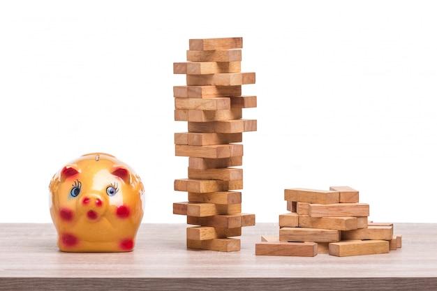 Stapel van blokken houten spel en spaarvarken op houten tafel.