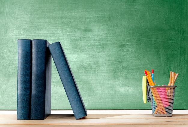 Stapel van boeken status en potloden in mandcontainer met groene nietmachine op de houten lijst