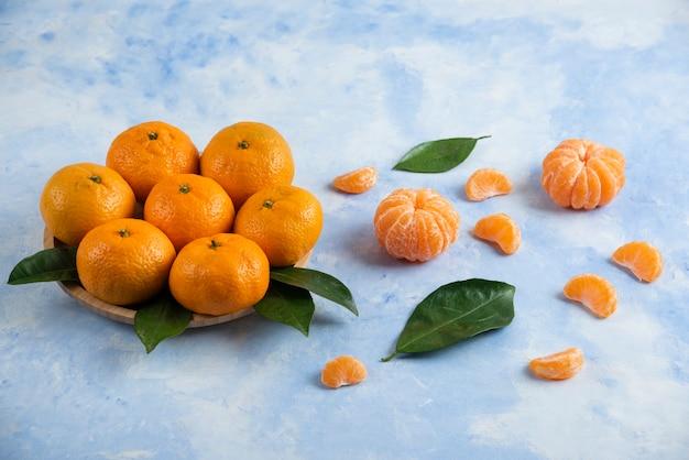 Stapel van clementine-mandarijnen op houten plaat en grond