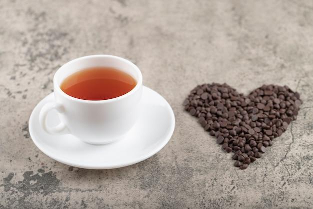 Stapel van donkere chocoladeschilferdruppels geplaatst als een hart met een kopje thee.