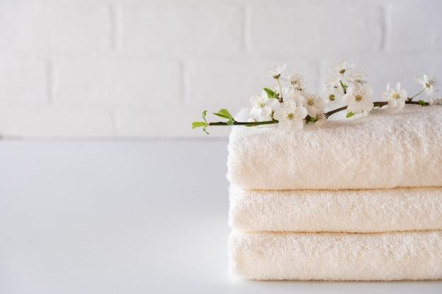 Stapel van drie witte pluizige badhanddoeken met tak. samenstelling van de spa ruimte kopiëren