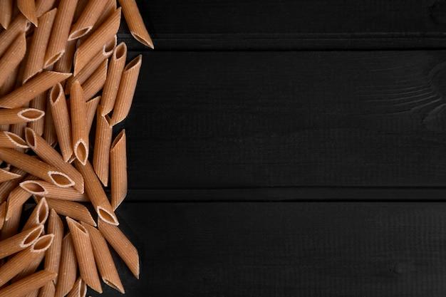 Stapel van droge ongekookte deegwaren die op donkere houten oppervlakte worden geplaatst. hoge kwaliteit foto