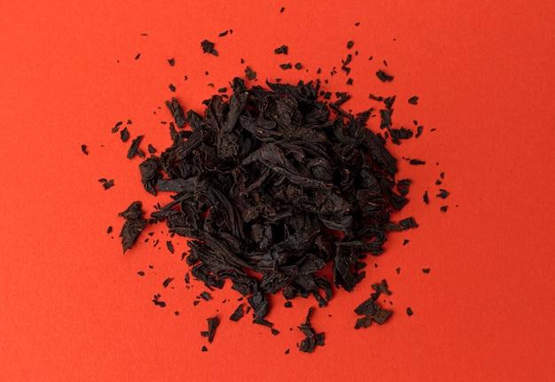 Stapel van droge theeblaadjes op rode achtergrond, bovenaanzicht