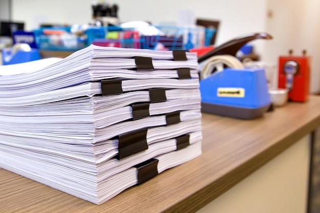 Stapel van een veel papier- en papierwerkrapport of afdrukdocument op het bureau van de bureaustapel.