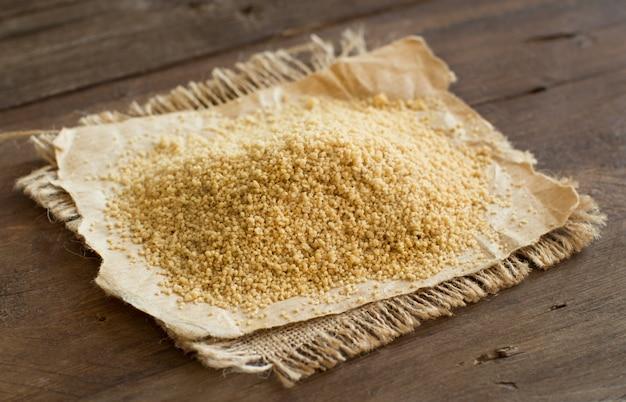 Stapel van gehele tarwe couscous op houten lijst dichte omhooggaand