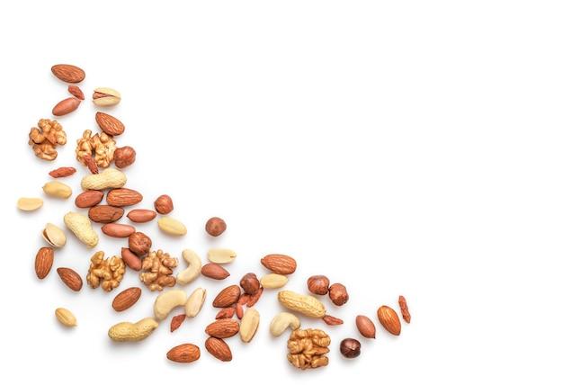 Stapel van gemengde noten op wit wordt geïsoleerd