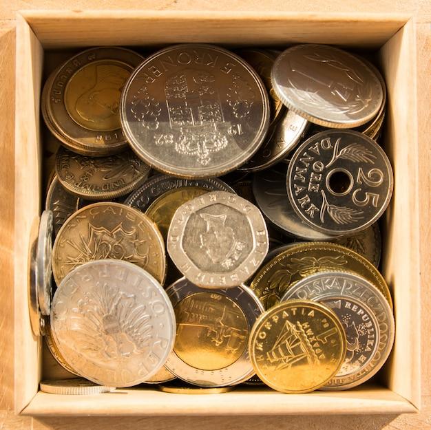 Stapel van gouden en zilveren munten in houten doos op de natuurlijke achtergrond.