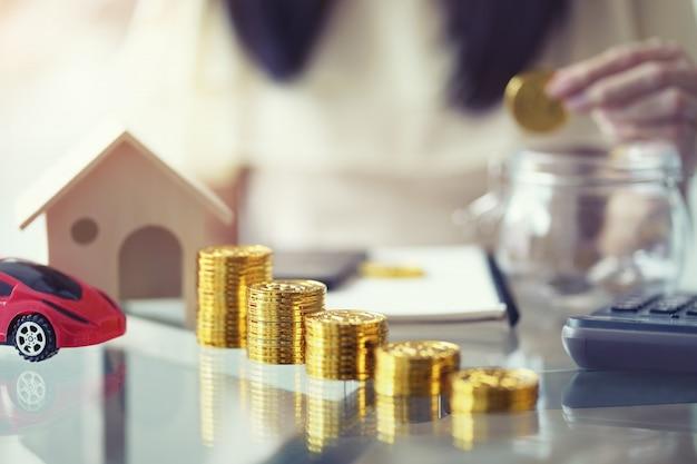 Stapel van gouden munten met houten huis