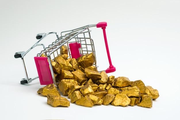 Stapel van goudklompjes of gouden erts in boodschappenwagentje of supermarktkarretje op witte achtergrond, edelsteen of stuk van gouden steen, financieel en bedrijfsconcept.