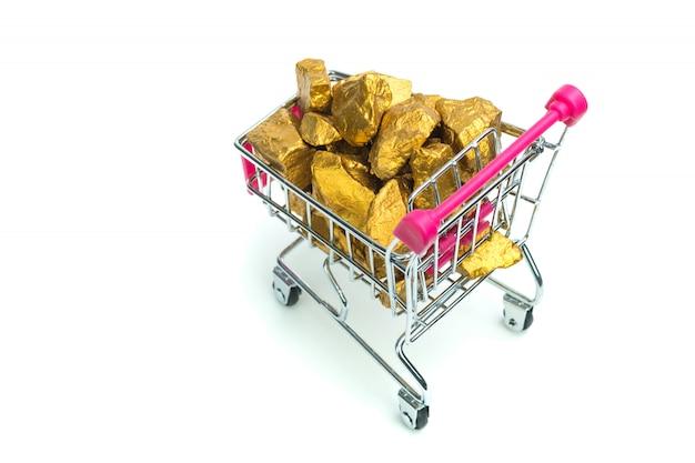 Stapel van goudklompjes of gouden erts in boodschappenwagentje of supermarktkarretje op witte achtergrond