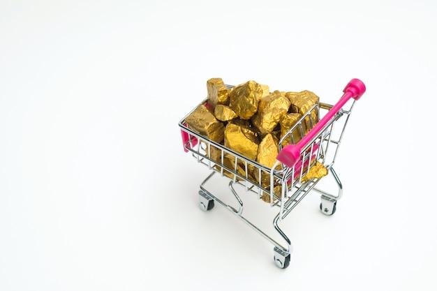 Stapel van goudklompjes of gouden erts in boodschappenwagentjekarretje op witte achtergrond