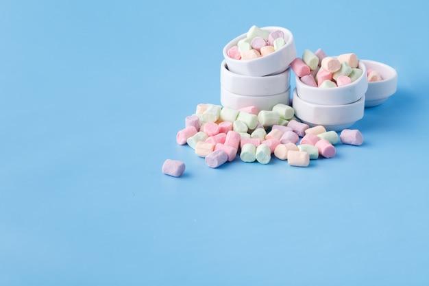 Stapel van kleine kleurrijke marshmallow op blauwe achtergrond in kom